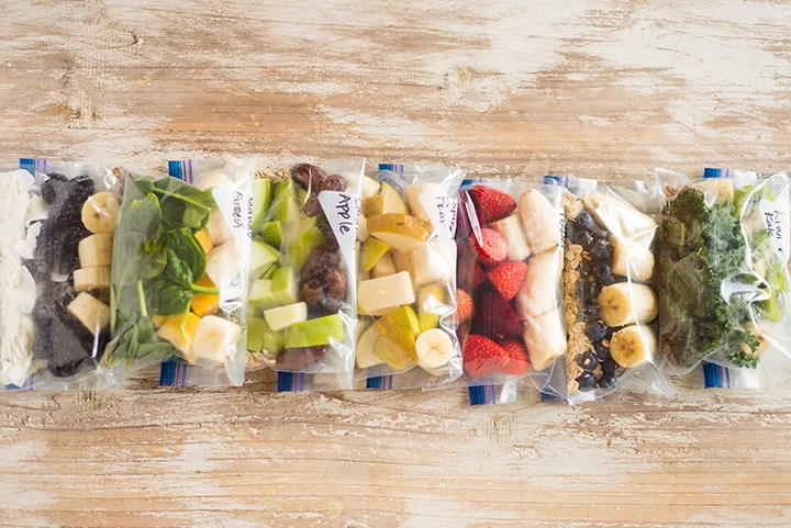 Fruit smoothie freezer packs lined up in a row on a counter, including kiwi and kale, pink power, caramel apple, blueberry muffin, spiced pear, and mango green fruit smoothie packs.